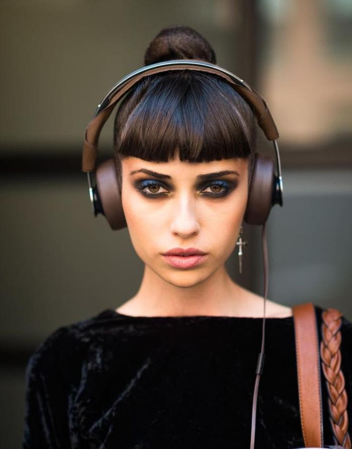 une coiffure femme frange graphique et chignon haut élégant pour une allure urbaine chic