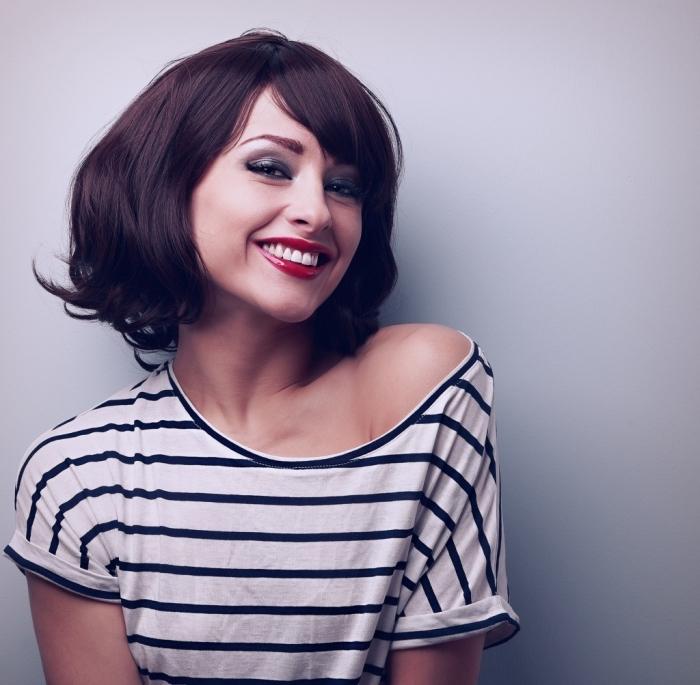 coupe de cheveux avec frange, maquillage aux lèvres rouges et yeux foncés avec fards à paupières de nuance verte foncée