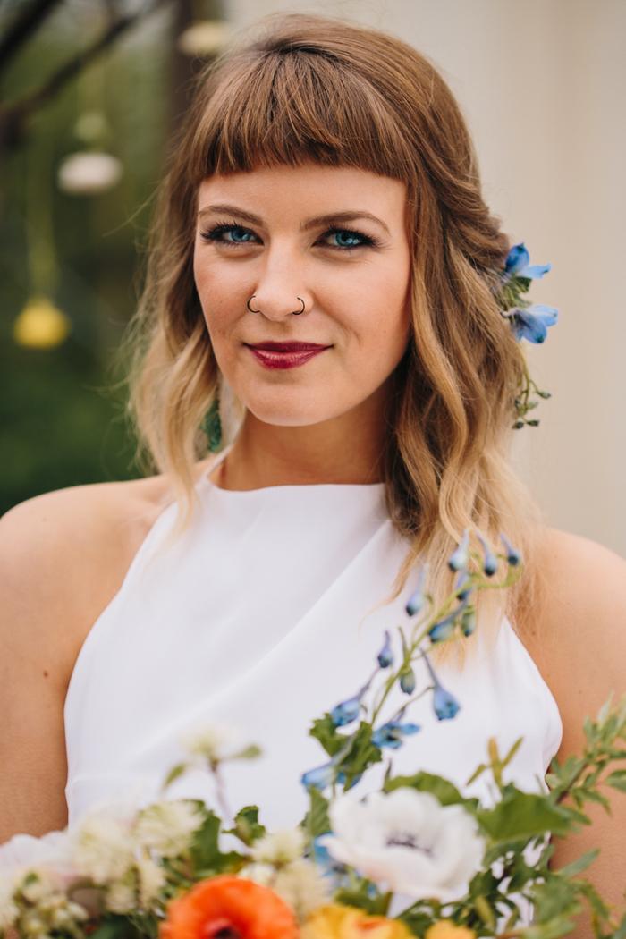 une coiffure de mariée qui affiche de jolies ondulations et une frange droite bien travaillée
