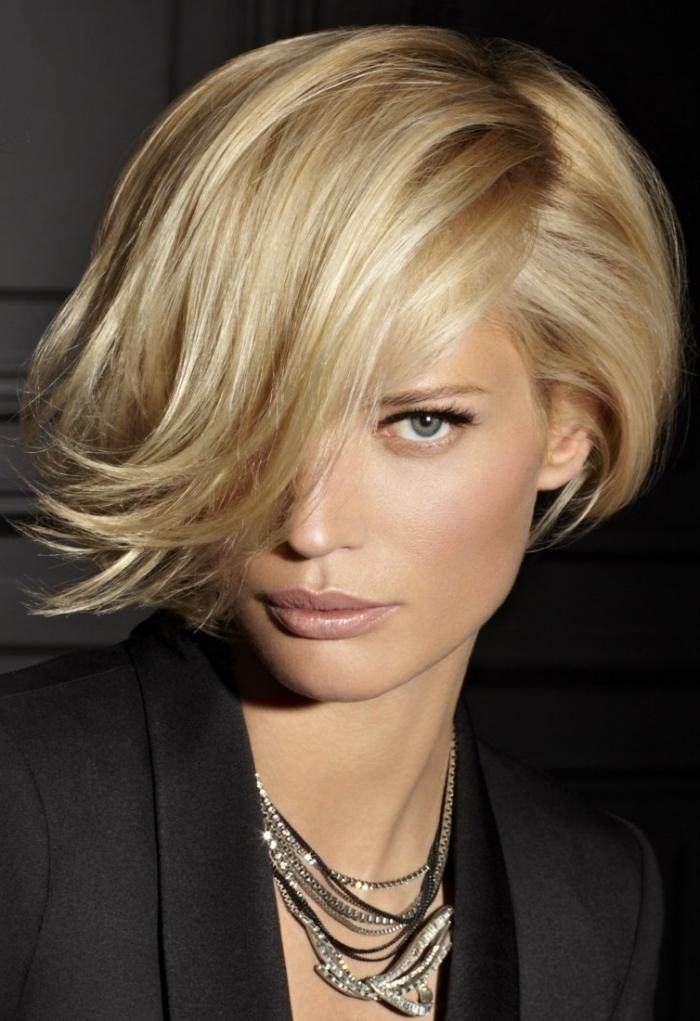 couper sa frange, coiffure féminine aux cheveux courts avec frange longue de côté, couleur de cheveux blond aux reflets miel