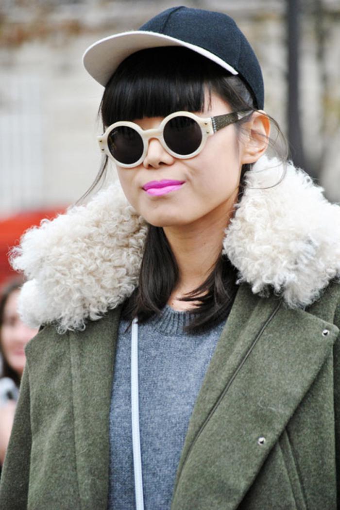 une frange droite et plate accessoirisé avec une casquette de baseball, des lunettes rondes à monture beige et rouge à lèvre rose