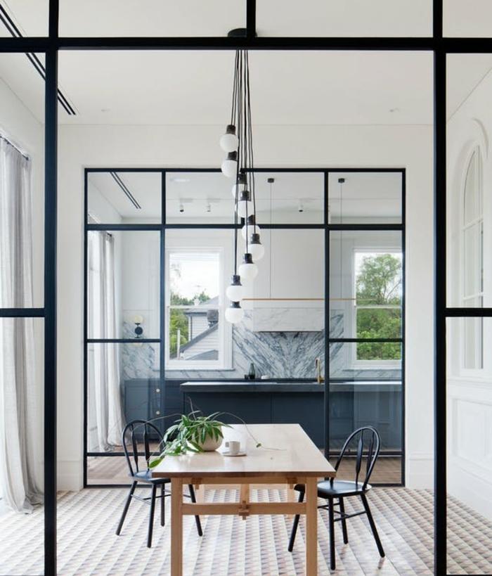 cuisine ouverte gris anthracite avec credence effet marbre et meuble blanc, separation par une verrière noire, table en bois et chaises metalliques noires, revêtement sol mosique à motifs geometriques, suspension ampoules electriques