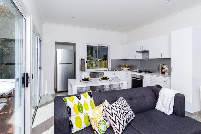 cuisine ouverte sur salon, facade meuble cuisine blanche et table de salle à manger blanche, credence grise, canapé gris dans le salon