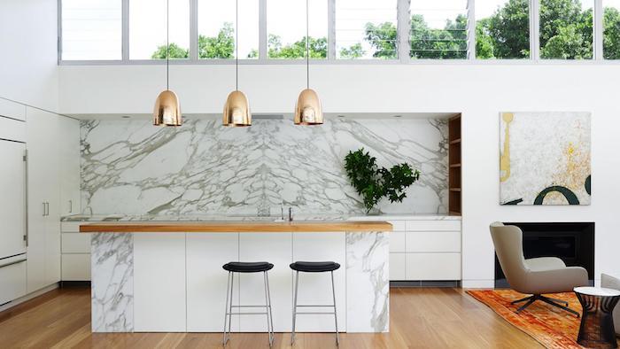 idee separation cuisine salon par un tapis coloré, fauteuil pivotant gris, table de service minimaliste, parquet clair, crédence et ilot central effet marbre, suspensions dorées