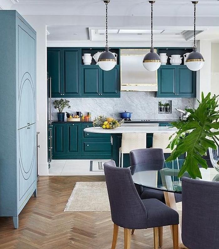 idee de deco facade cuisine, nuance de bleu, crédence en marbre, ilot central bleu vert, parquet clair, suspensions originales, table en bois et verre et chaises violettes