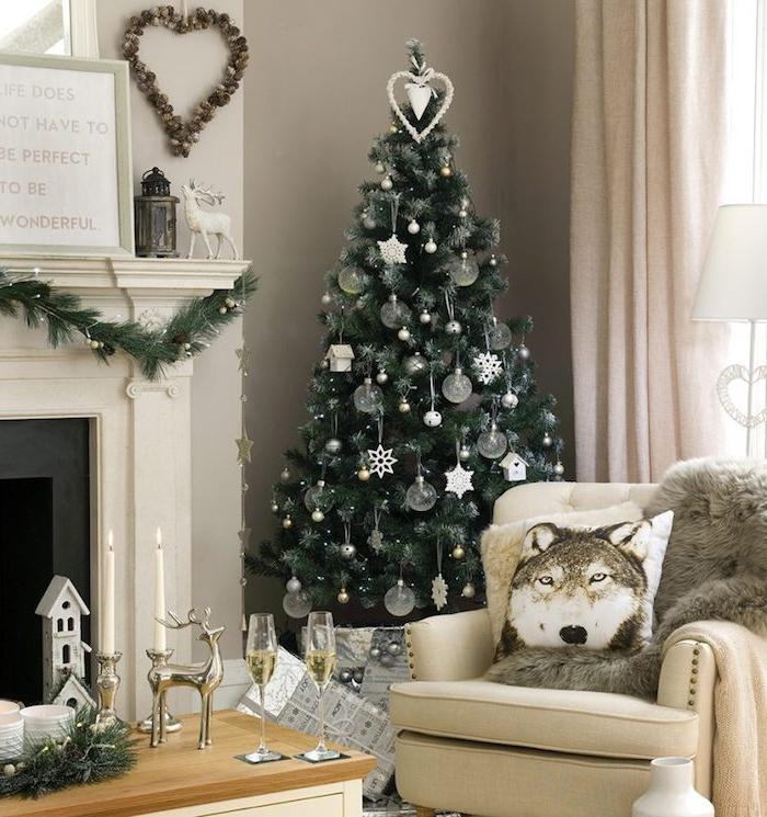 deco sapin de noel en boules de noel transparente, flacons de neige et étoiles blanches, cheminée blanche, fauteuil beige et table basse en bois