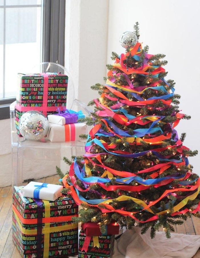 decoration sapin de noel en guirlandes de rubans rouges, bleus et jaunes et guirlande lumineuse, paquets cadeaux noirs avec lettres colorés