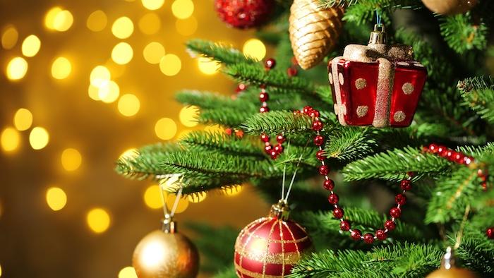 comment décorer un sapin de noel, idées, conseils et tutoriels, guirlande de perles rouges, pommes de pin, boules de noel et ornements rouges et dorées