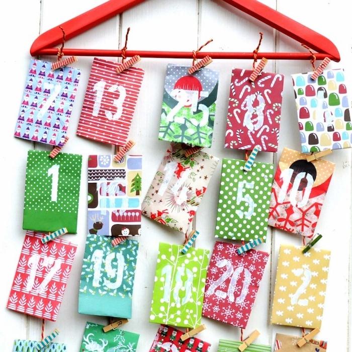 idée comment fabriquer un calendrier de l avent, deco noel a faire soi meme, cintre rouge avec des sachets colorés avec chiffres