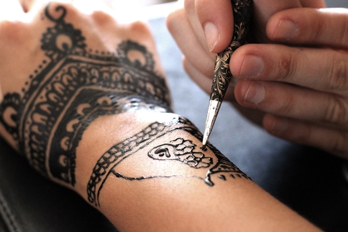 tatouage henné noir, technique de dessiner sur la peau au henné noir, tatouage sur mains pour femme