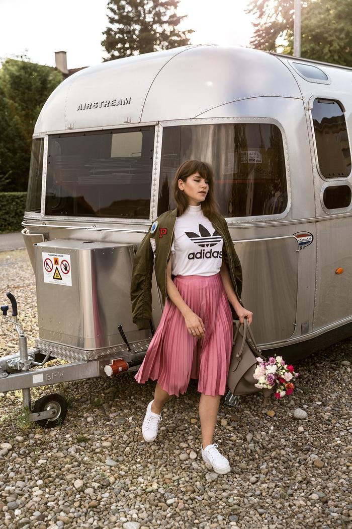 look urbain chic avec jupe plisée rose bonbon, t-shirt adidas et une veste aviateur femme à broderies de styme bomber