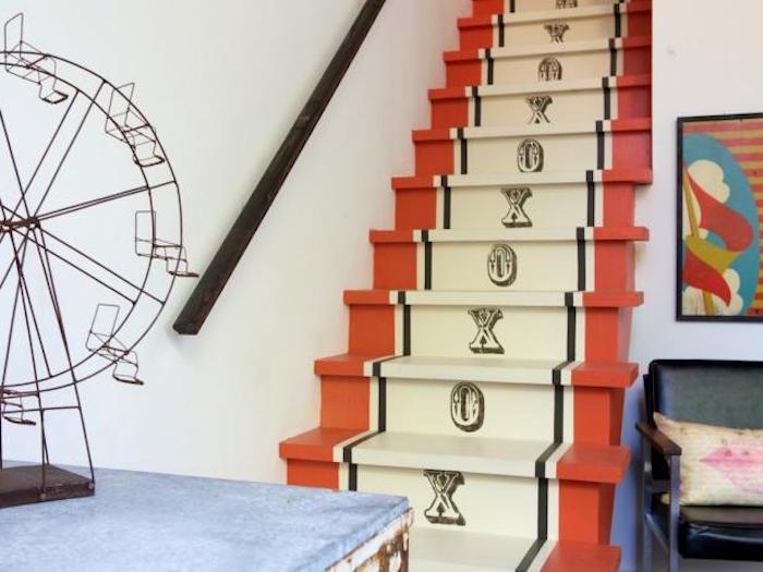 idée comment repeindre un escalier à motif intéressant, rayures rouges, jaunes et noires, stampe en lettres, main courante en bois