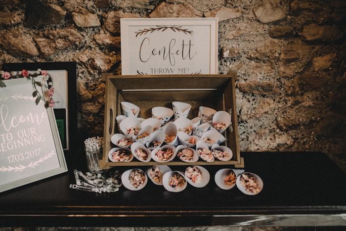 cornets en papier remplis de confettis, fleurs séchées sur une cagette bois, mur en pierre sur le fond