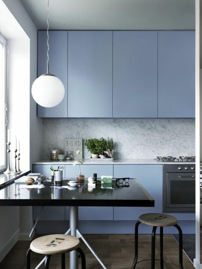 nuance de bleu couleur bleu gris avec des meubles de cuisine en bleu gris luminaire boule blanche grande table carrée en noir finition lustrée