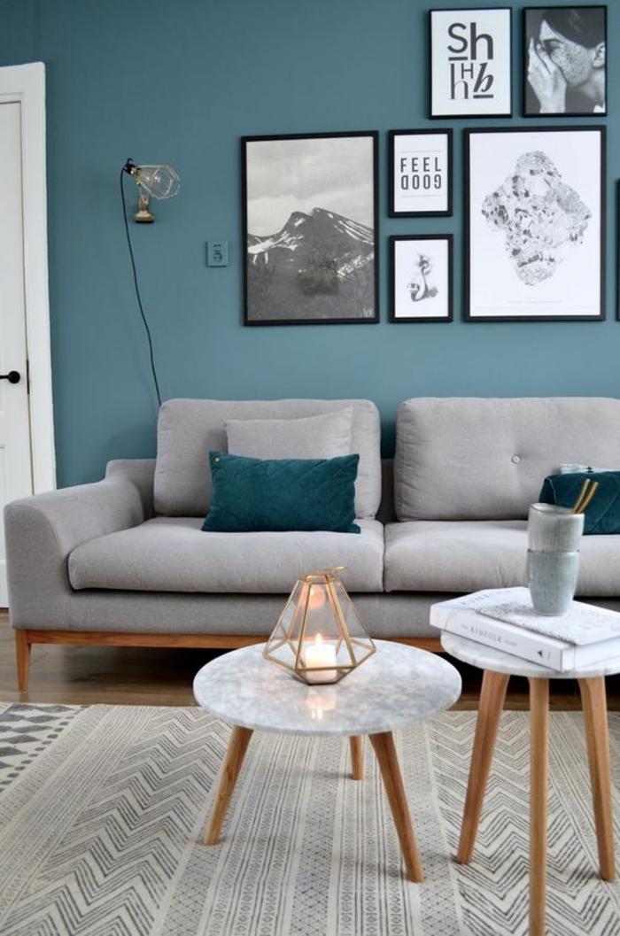 salon bleu petrole aux murs et meubles en couleurs claires gris clair et blanc pour les deux tables rondes de tailles diverses