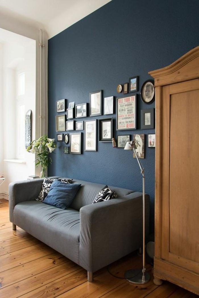 salon bleu petrole avec canapé en gris clair et grande armoire en marron clair mur coloré avec une multitude de tableaux en cadres ronds et carrés