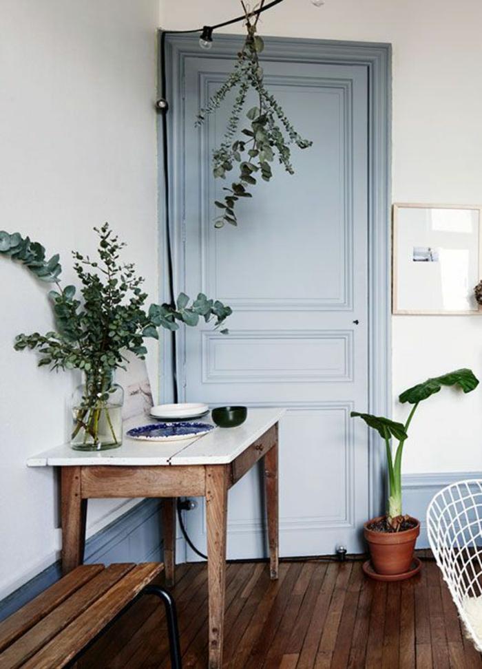 couleur bleu gris porte peinte dans une entrée aux murs blancs avec leur partie bases peinte en bleu canard