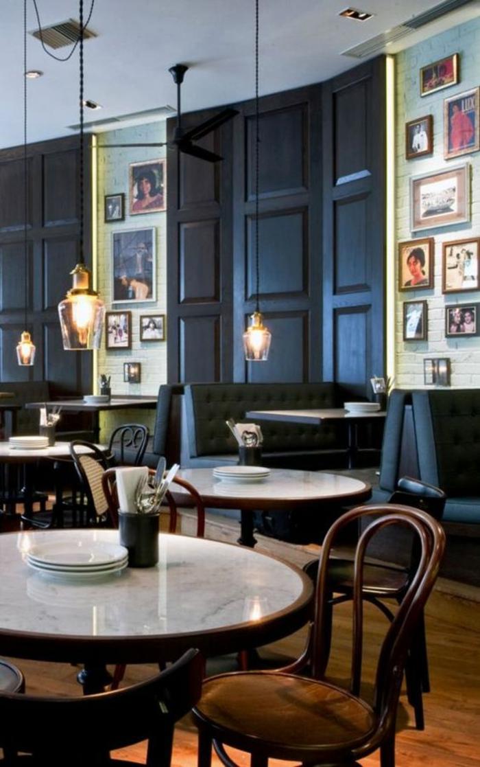 couleur bleu gris dans un restaurant bistrot avec des luminaires suspendus en verre transparent avec des grandes ampoules et des chaises de bistrot en bois style traditionnel