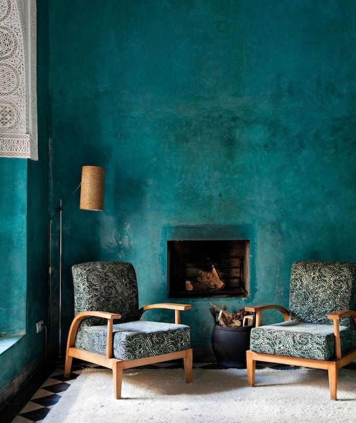 idée de mur de fond bleu petrole peinture, chaises en bois, revêtement chaise à motifs floraux gris, vert et noir, tapis blanc cassé et cheminée rustique