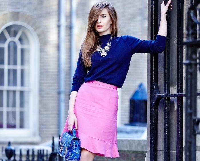 couleurs complémentaires, femme au pull bleu foncé et jupe rose courte avec sac à main bleu et cheveux longs marron