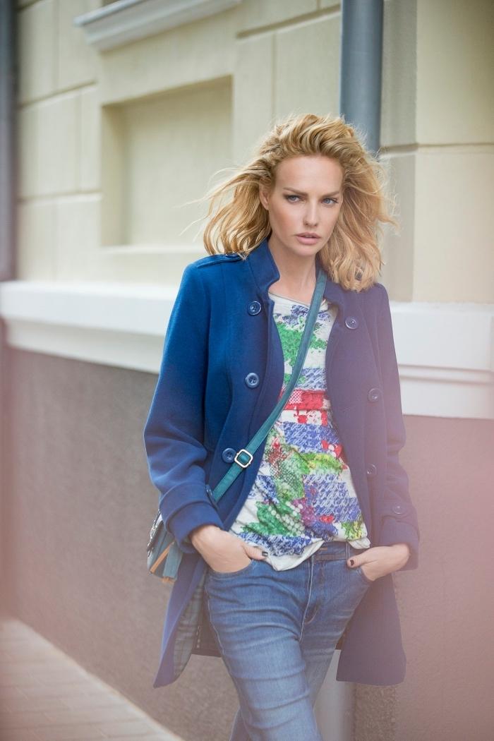 coupe de cheveux femme mi longs, coloration cheveux blond foncé, manteau mi long en bleu foncé avec paire de jeans clairs