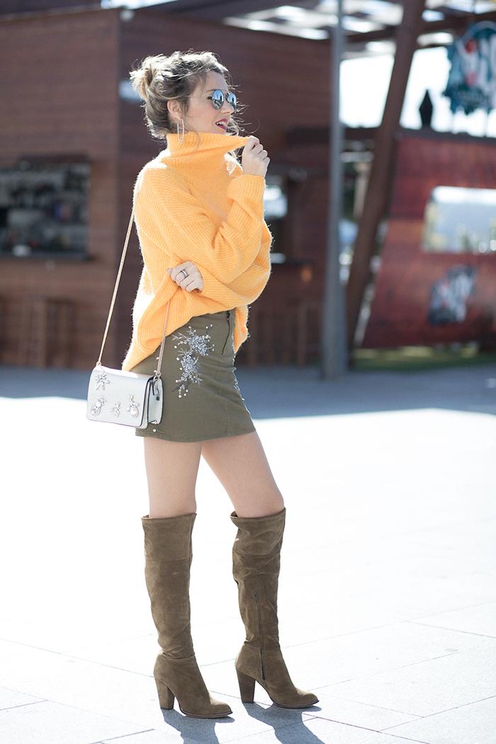 une façon originale d'assortir le kaki vert et les nuances vives, un pull oversize en tangerine associé à jupe courte kaki brodée et des cuissardes en suédine marron