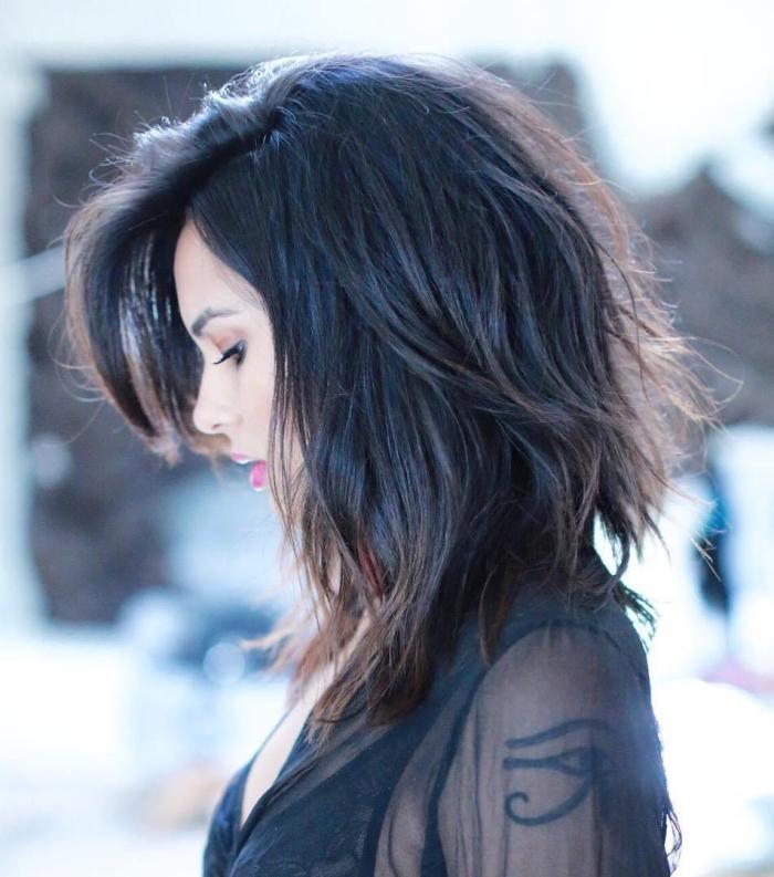 frange sur le côté, couleur de cheveux noir avec reflets châtain, coupe femme aux cheveux mi longs
