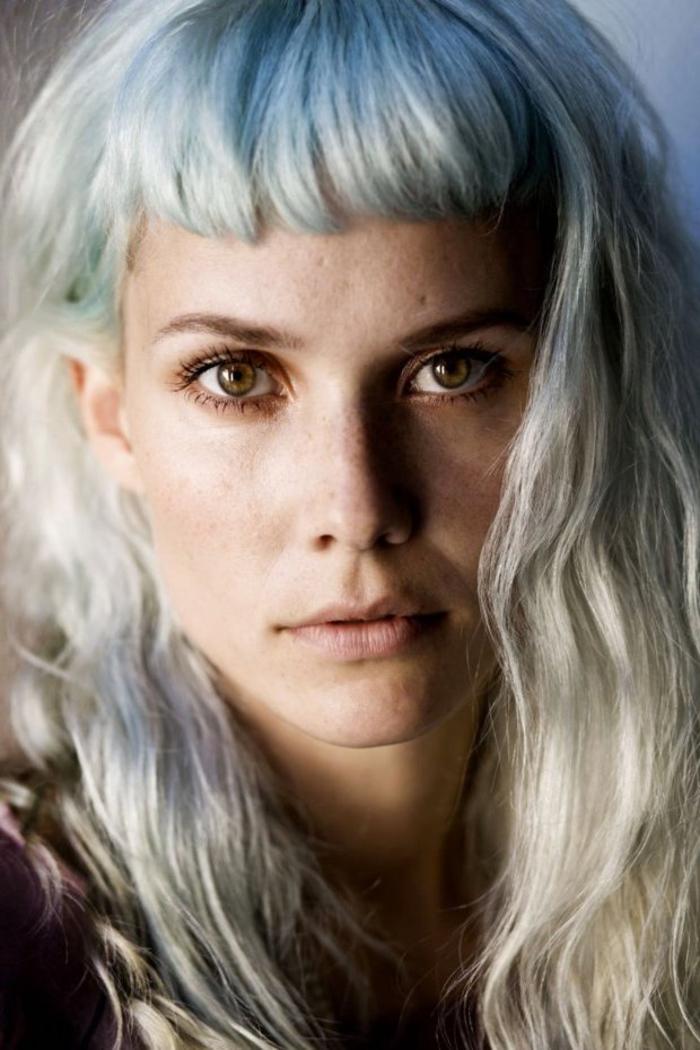 une coupe de cheveux avec frange minimaliste et des reflets bleus dans les cheveux blond polaire