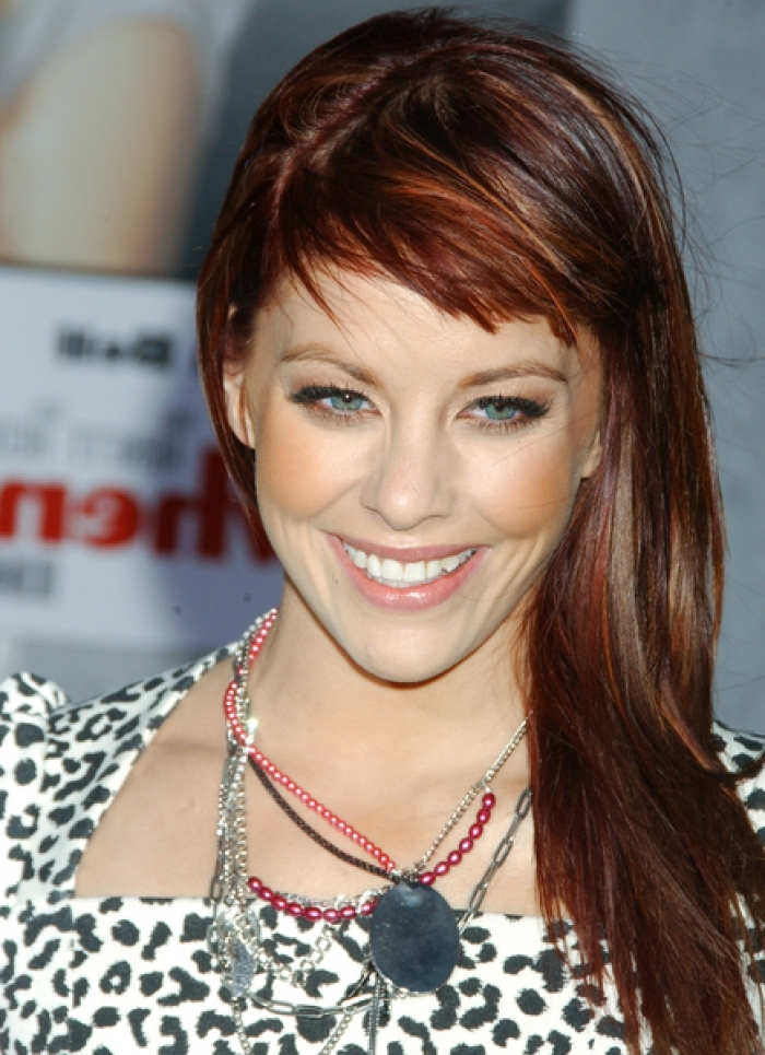 des cheveux longs aux nuances du roux porté de côté avec une frange effilée  asymétrique