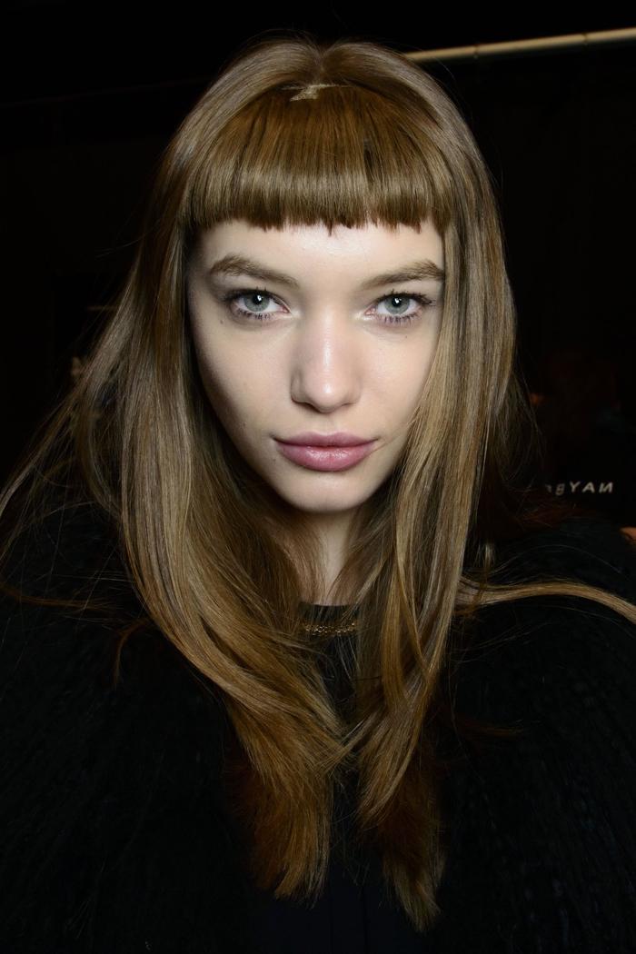 une coiffure sublime avec une frange droite et légèrement bombée qui met accent sur les yeux et la beauté naturelle du visage