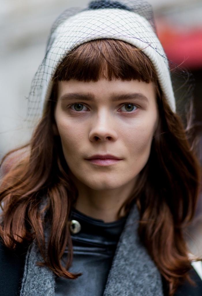 une coupe de cheveux avec frange graphique portée de façon casual sous un bonnet à voilette