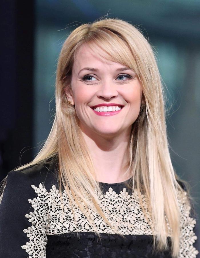 coiffure célébrité Reese Witherspoon, couleur de cheveux blond avec mèches dorées, robe noire aux manches longues avec décoration en broderie blanche