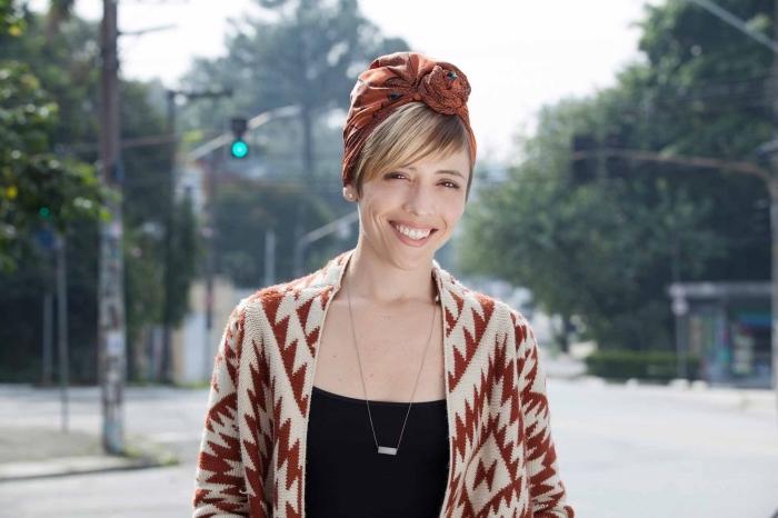 coiffure courte avec frange, couleur de cheveux châtain foncé avec mèches blondes, tenue femme en poncho et débardeur noir