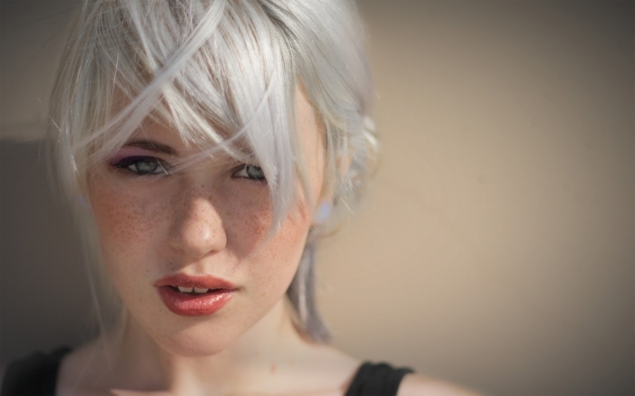 frange sur le côté, couleur de cheveux gris, coiffure cheveux attachés en chignon décontracté avec mèches devant