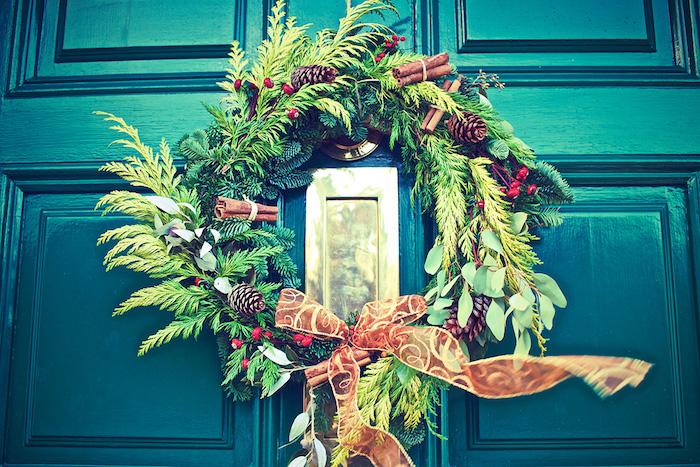 couronne de noel de branches de pin avec des pomems de pin, houx, cannelle et ruban marron sur une porte vert emeraude, fond d ecran noel