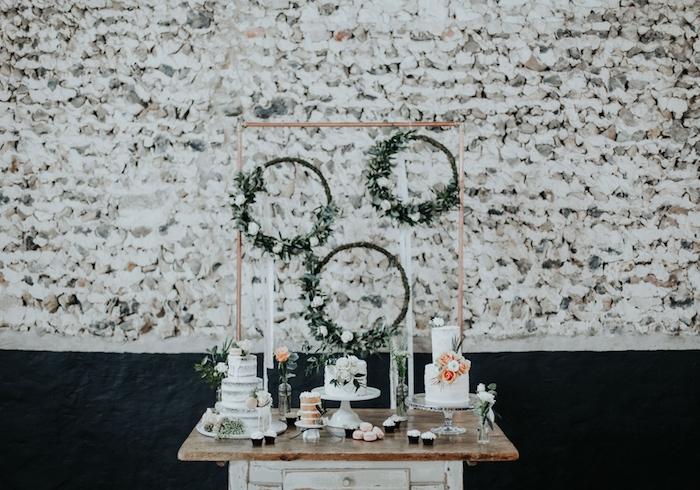 couronnes avec fleurs blanches et feuillages sur une table vintage en bois brut, gâteau fleuri, mur en pierre sur le fond