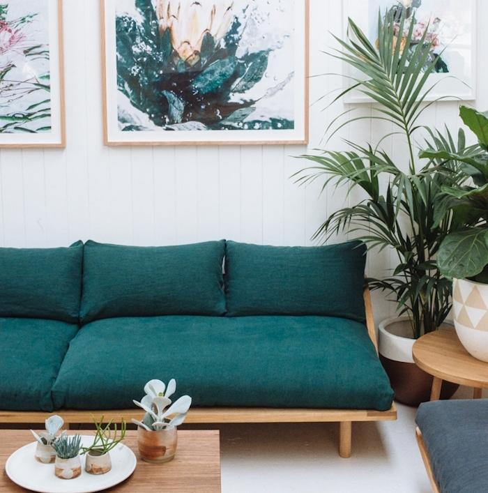 idée de canapé bleu pétrole tirant vers le vert, table basse en bois, plantes vertes, lambris blanc et deco murale tableaux de peinture motif naturel