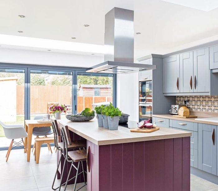 modele de cuisine ouverte avec façade bleu gris, crédence en mosaique orientale, bar mauve avec plan de travail bois, salle à manger avec chaises scandinave et table en bois, aspirateur inox