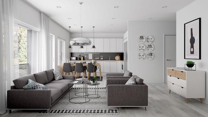 aménagement petite cuisine ouverte blanche avec crédence grise, salle à manger avec table en bois et chaises grises, canapé et fauteuils gris, tables basses noires gigognes