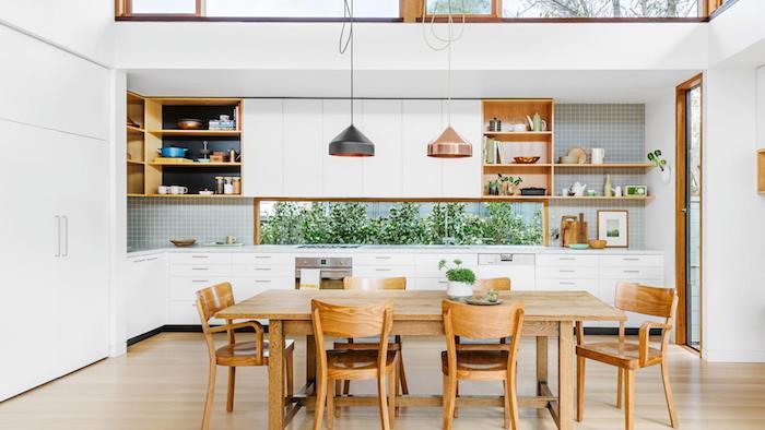 idée de cuisine americaine blanche et bois avec des etageres rangement vaisselle ouvertes, table et chaoses en bois sur un parquet clair