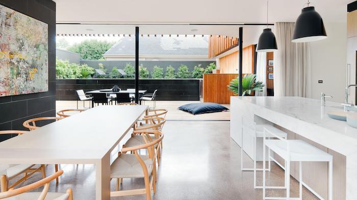 comment aménager une cuisine en longueur blanche avec ilot central effet marbre, salle à manger en table et chaises en bois, suspensions grises industrielles