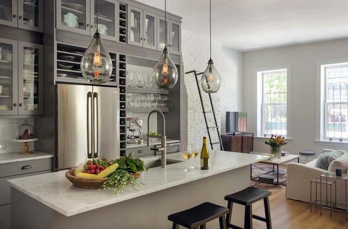 cuisine avec bar gris et plan de travail en marbre, façade cuisine grise, électroménager en inox, suspensions originales, canapé blanc, table en bois et metal