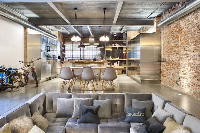 cuisine americaine style industriel, cuisine gris et bois ouverte sur salle à manger chaises scandinaves et table en bois, canapé d angle gris, mur en briques