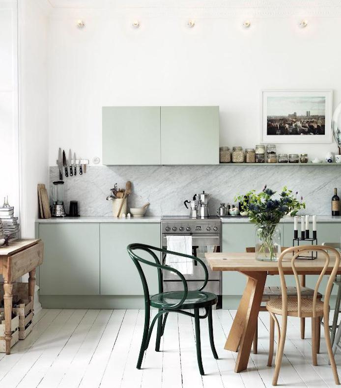 cuisine americaine vintage avec façade cuisine vert menthe et crédence grise, parquet clair blanchi, table en bois avec chaises en bois et metal