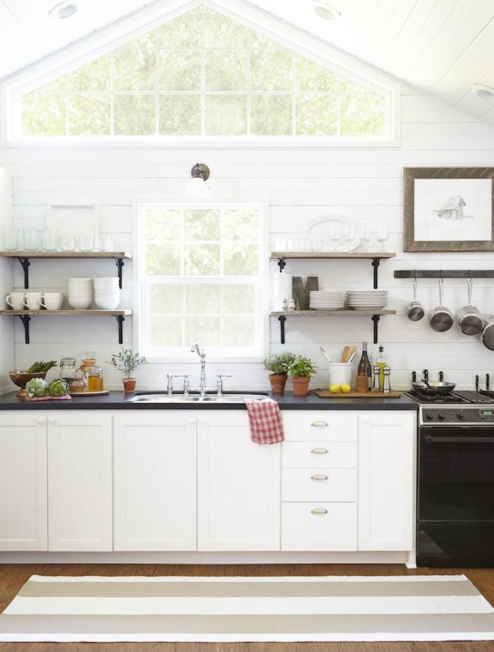 modele de cuisine ancienne style campagne, façade meuble cuisine blanche et fourneau noir, étagères en bois et metal avec vaisselle blanche et casseroles exposées, plan de travail noir