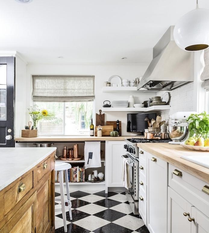 cuisine style campagne avec meuble blanc, ilot central en bois et plan de travail blanc, électroménager inox, étagères ouvertes blanches et vaisselle en pleine vue, sol en carrelage noir et blanc