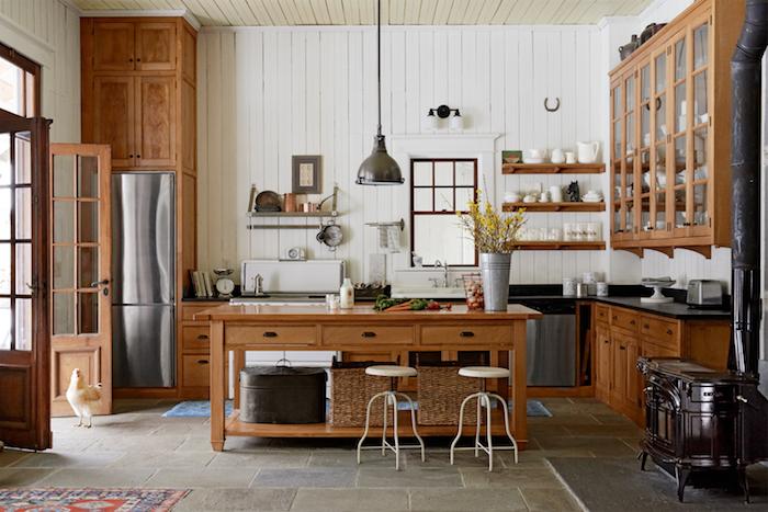 cuisine rustique avec facade meuble cuisine bois marron, ilot central cuisine, entouré de tabourets, mur à lambris blanc, dallage de pierre, etagres bois ouvertes, vaisselle blanche exposée, poule