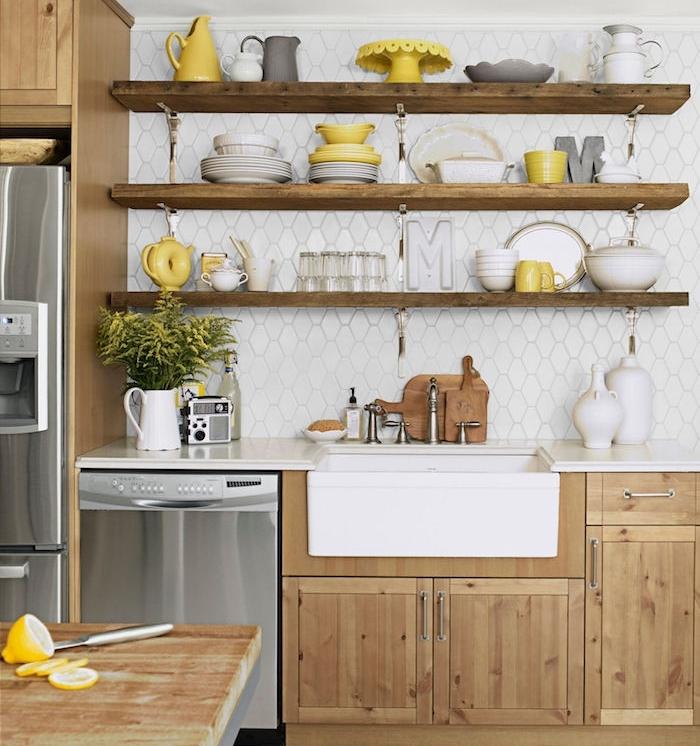 cuisine campagnarde en ois clair avec etagere bois, surchargée de vaisselle blanche et jaune et grise, plan de travail blanc, robinetterie vintage