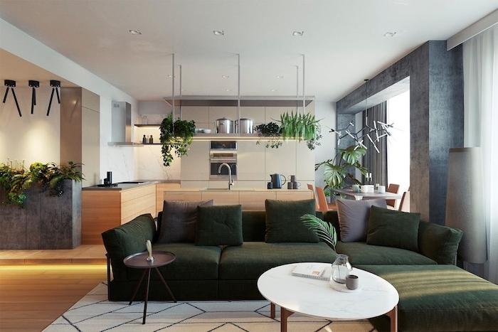 modele de cuisine grise avec bar en bois, canapé d angle vert émeraude, table en bois avec plateau marbre, éclairage Led s au sol, plusieurs plantes vertes