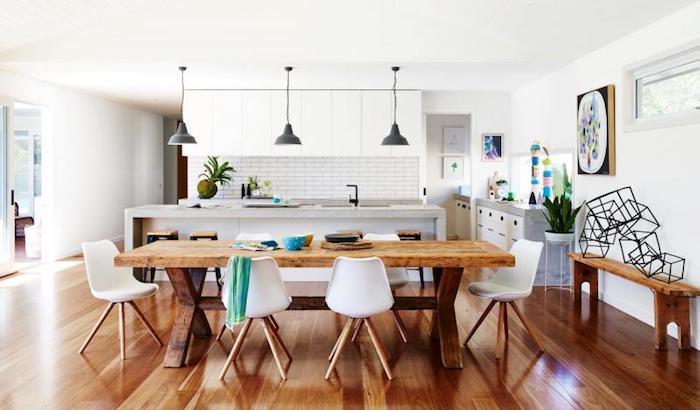 aménagement cuisine avec bar, couleur façade blanche, table en bois rustique et chaises scandinaves, parquet marron, suspensions industrielles